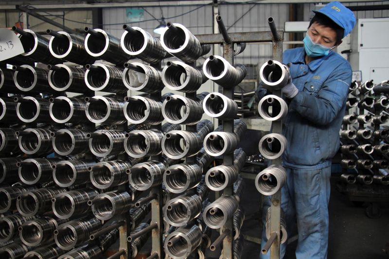 A worker in China readies aluminum pistons for manufacturing.