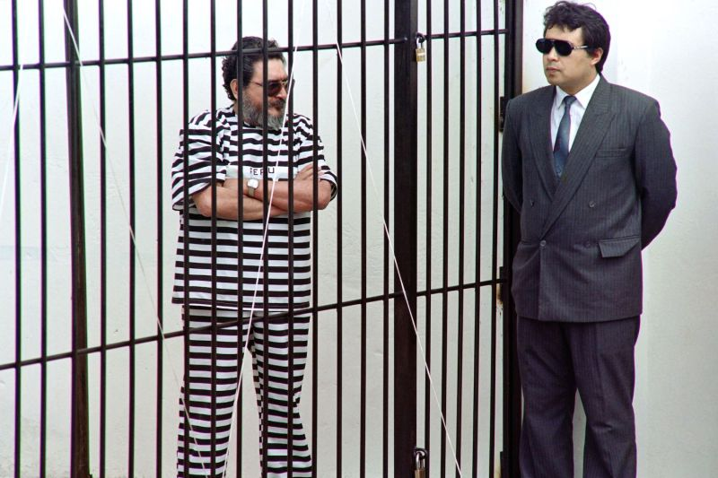 Leader and founder of the Shining Path terrorist group Abimael Guzmán talks to a Peruvian anti-terrorist policeman in jail in Lima on Sept. 24, 1992.