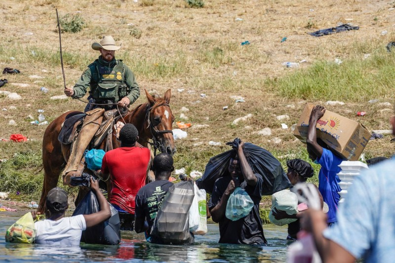 A United States Border Patrol agent on horseback with Haitian migrants