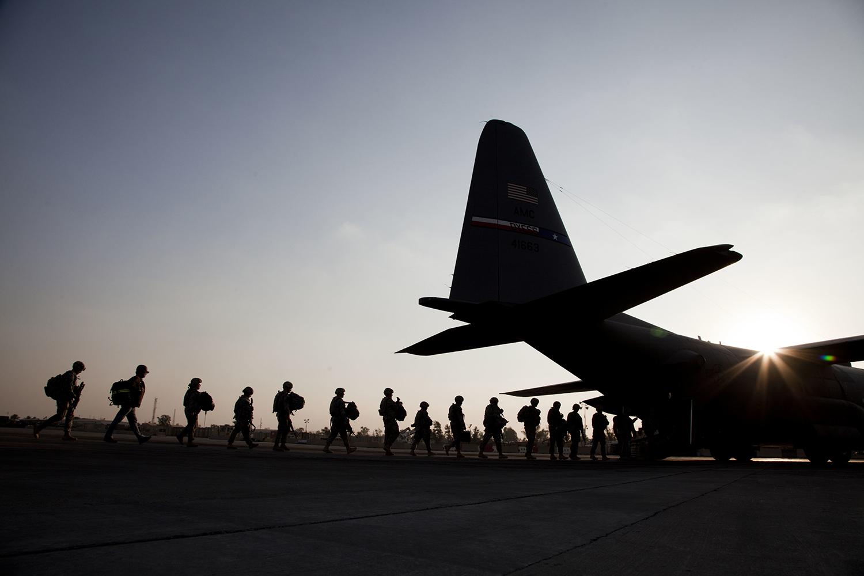 American soldiers board a U.S. Air Force C-130 plane.