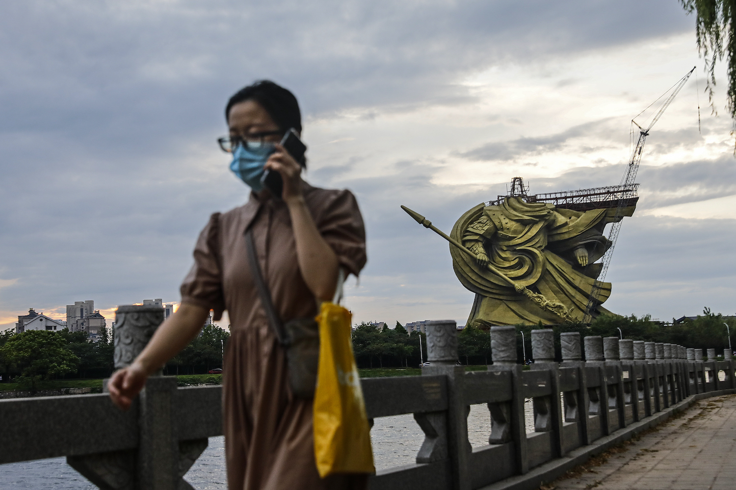 A woman walks by as workers dismantle the giant statue of Guan Yu in Jingzhou, China, on Sept. 6.