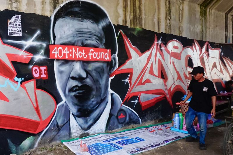 """A mural depicts Indonesian President Joko Widodo with the network error message """"404: Not found"""" covering his eyes."""