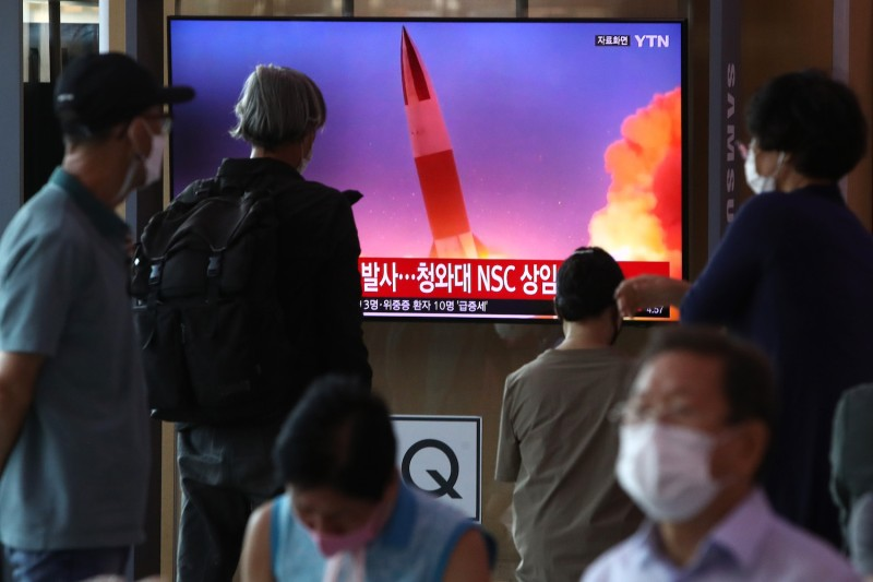 People watch a TV showing an image of a North Korean missile launch