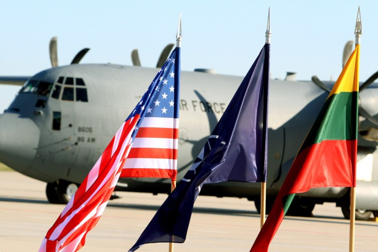 Flags of Lithuania, the United States, and NATO are hoisted in front of a U.S. Air Force plane carrying U.S. soldiers at the air force base near Siauliai Zuokniai, Lithuania, on April 26, 2014.