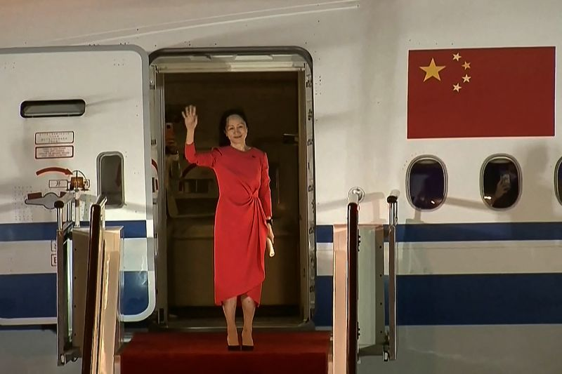Meng Wanzhou dressed in a red dress waves as she steps out of a plane with a Chinese flag on the side of it.