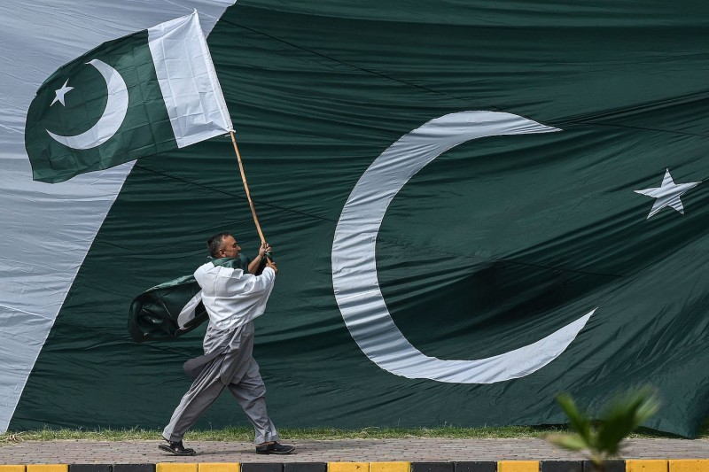 A man holds the national flag of Pakistan