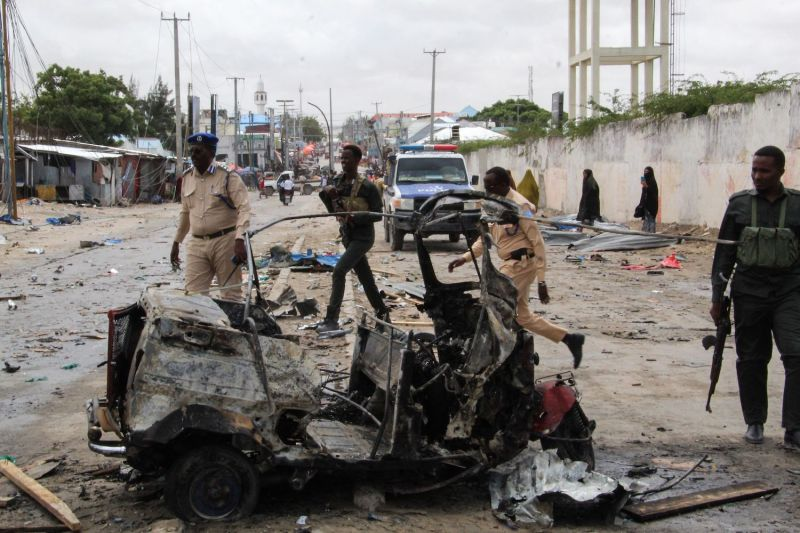 Police officers patrol by the wreckage of a car at the scene of suicide car bomb attack that targeted the city's police commissioner in Mogadishu, on July 10.
