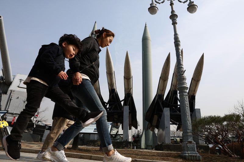 South Koreans walk past replicas of missiles at the Korean War Memorial.