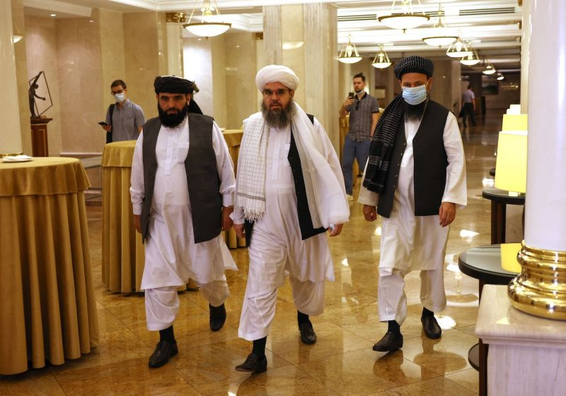 Taliban leaders walk toward a Moscow press conference.