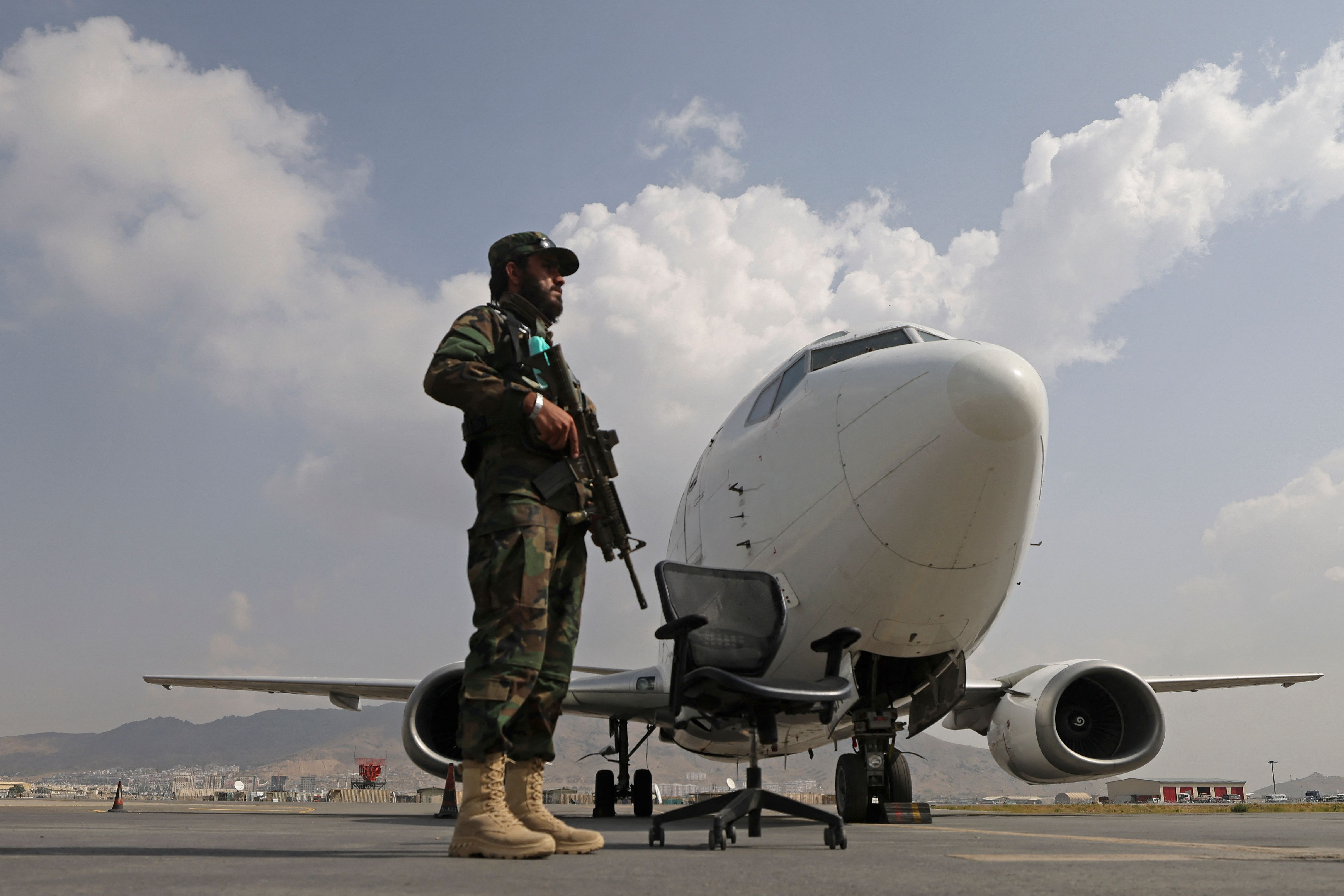 A Taliban fighter stands guard on the tarmac at the airport in Kabul on Sept. 12.