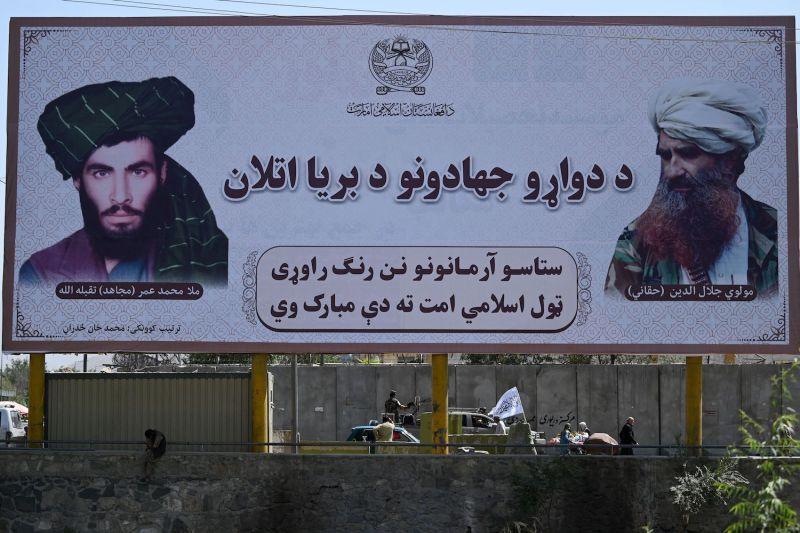 Taliban fighters pass a billboard in Kabul.
