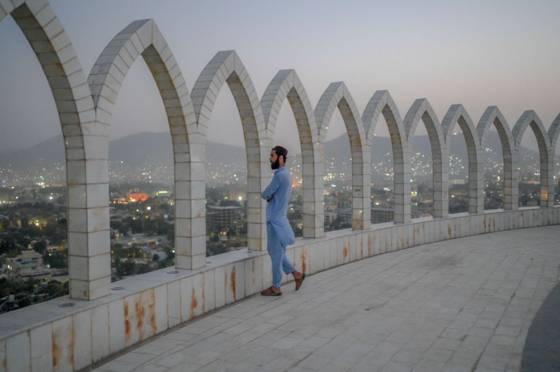 A man dressed in a blue tunic and pants gazes out over a view of the city through peaked arches atop a high building.