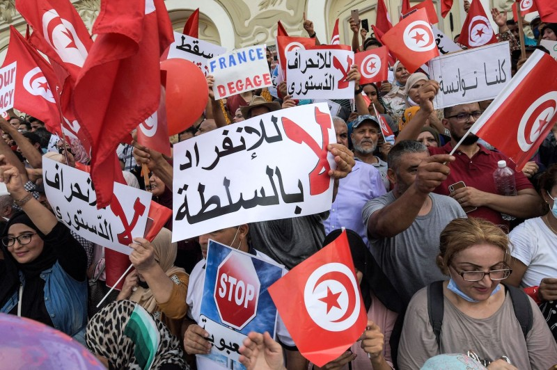 Protesters hold Arabic signs and wave Tunisia's flag during a demonstration.