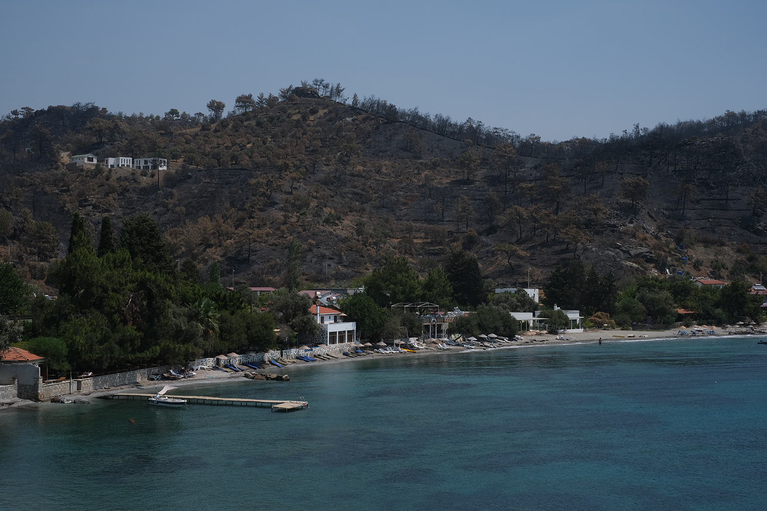 The hills behind behind Mazikoy, Mugla, are seen blackened by forest fires