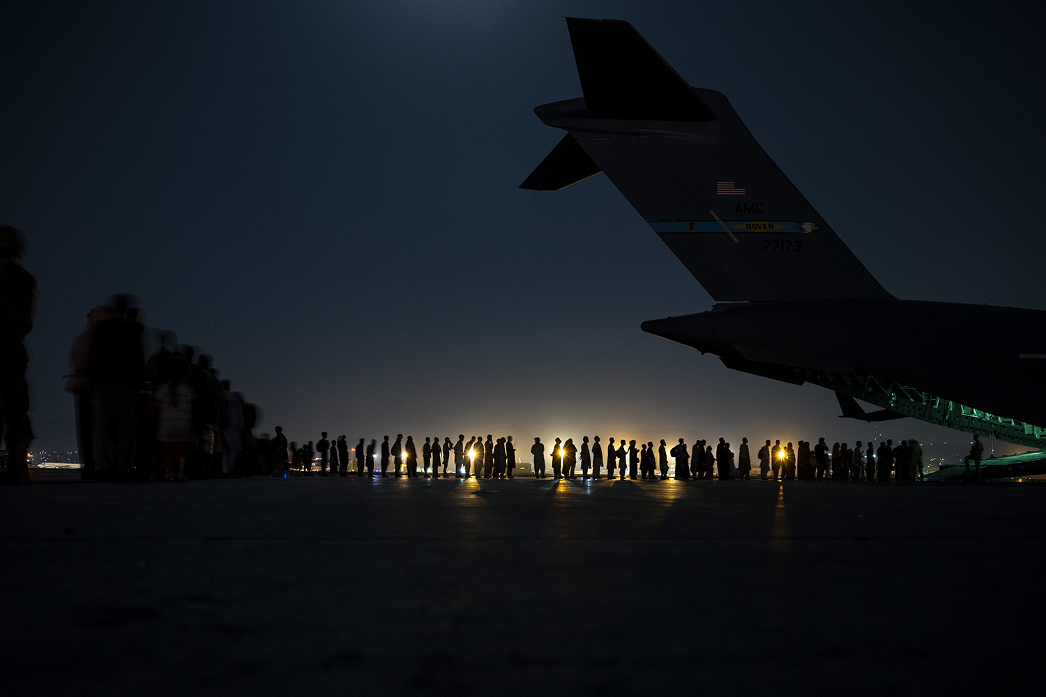 An air crew prepares to load evacuees aboard a C-17 Globemaster III aircraft.