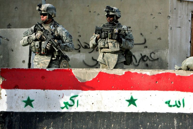 Two U.S. soldiers walk past a concrete block with a painted-on Iraqi flag as they patrol a neighborhood in Baghdad on Jan. 18, 2008.