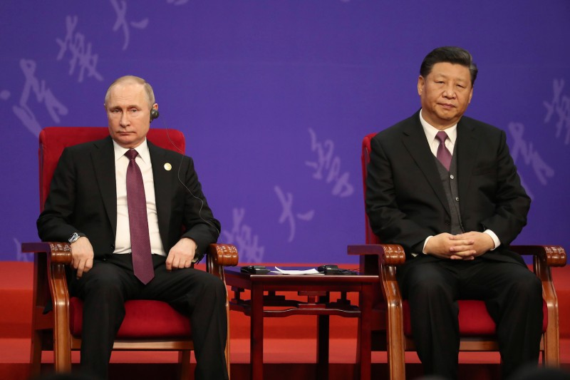 Vladimir Putin and Xi Jinping sit slightly slumped in red chairs next to one another.