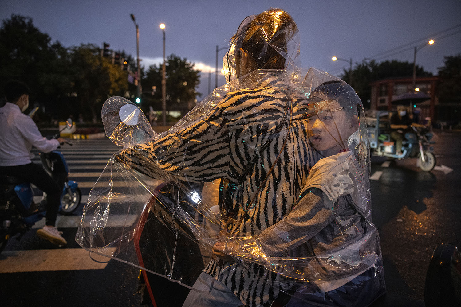 A boy sits inside his mother's plastic raincoat as they wait to cross at a traffic light during a rainstorm in Beijing on Sept. 8. Kevin Frayer/Getty Images