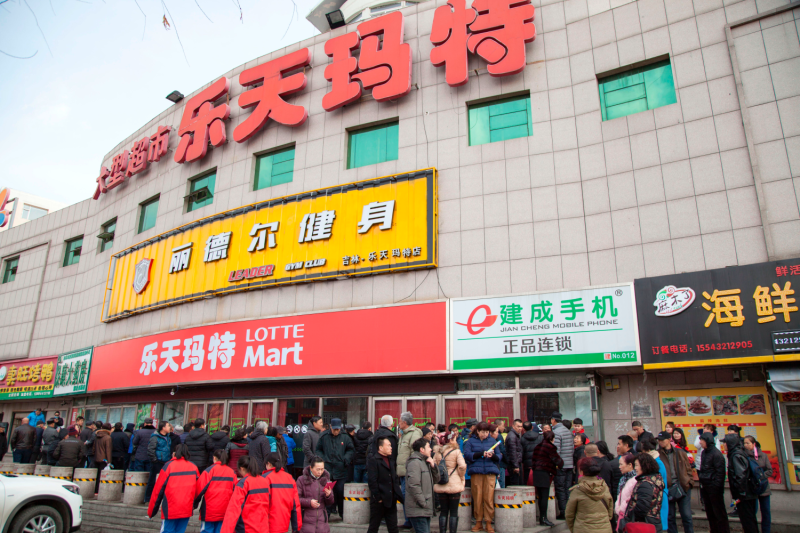 People stand outside a closed Lotte store.