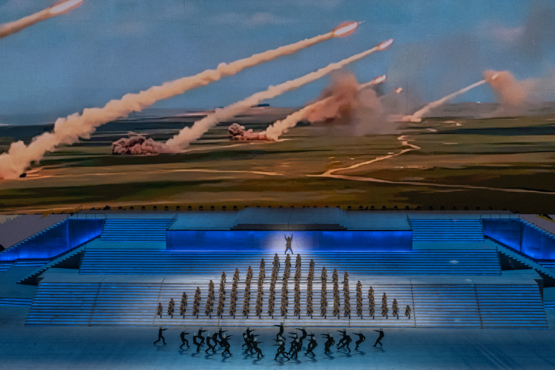 Performers dressed as soldiers perform in front of a screen showing rockets being launched during a mass gala marking the 100th anniversary of Chinese the Communist Party in Beijing on June 28.