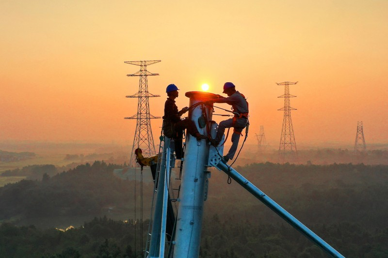 Employees work on a high-voltage transmission tower in China.