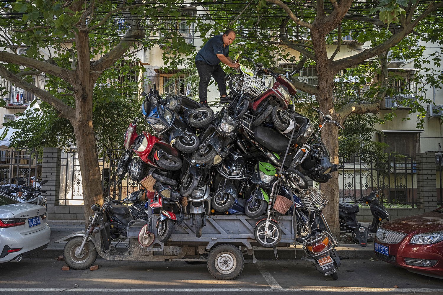 A worker piles salvaged electronic bikes and scooters on the back of his truck before taking them to be recycled in Beijing on Aug. 31. Kevin Frayer/Getty Images