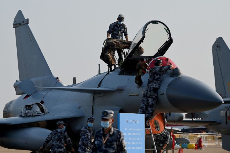 Military personnel prepare to cover a Chengdu Aircraft J-10C.