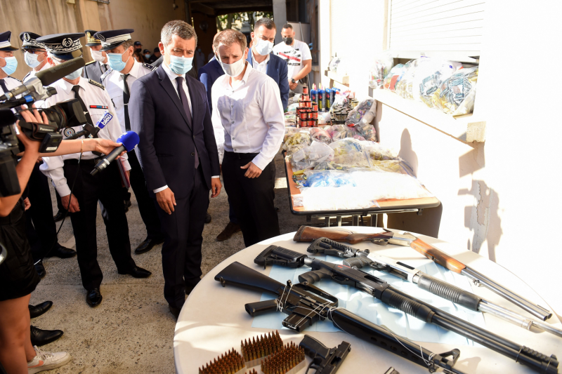 A police officer shows drugs and weapons to French Interior Minister Gérald Darmanin