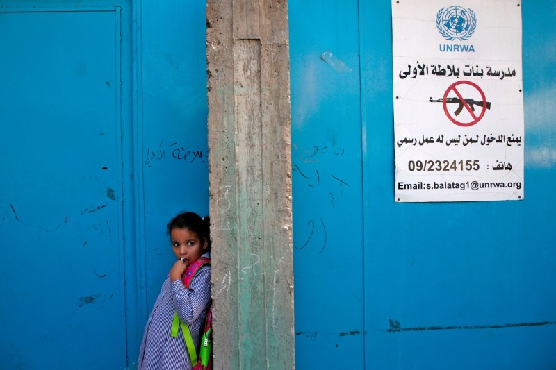 A pupil stands at the entrance of a school run by the United Nations Relief and Works Agency in the Balata refugee camp in the occupied West Bank on Aug. 29, 2018.