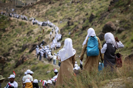 Yemeni volunteers form a human chain to pass food aid to mountainous towns on the outskirts of Taiz, Yemen, on Oct. 16, 2018.