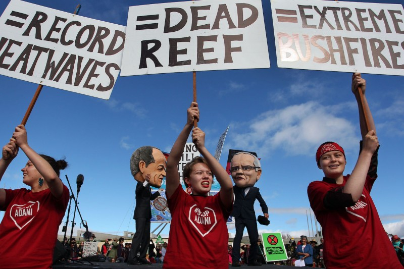 Young environmental activists hold protest signs up in front of comedians dressed as Australian Labor leader Bill Shorten and Prime Minister Scott Morrison in Canberra, Australia, on May 5, 2019.