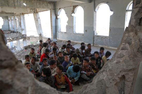 Yemeni children listen to their teacher on the first day of school in a destroyed classroom in Taiz, Yemen, on Sept. 3, 2019.