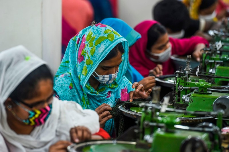 Laborers wearing face masks work in a garment factory in Ashulia, Bangladesh, on April 7, 2020.