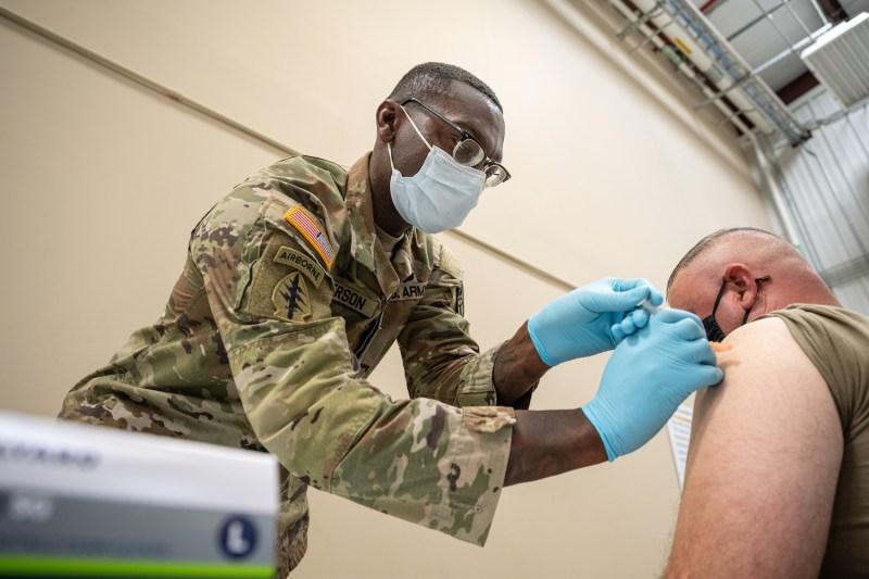 A preventive medicine services sergeant administers a COVID-19 vaccine.