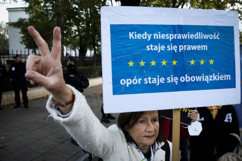 A demonstrator flashes the victory sign in front of the Constitutional Court in Warsaw, Poland.