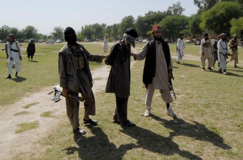 Pakistani Taliban escort a kidnapper as they arrive for his execution at the Rahim Kor village near Peshawar, Pakkistan on April 27, 2008.