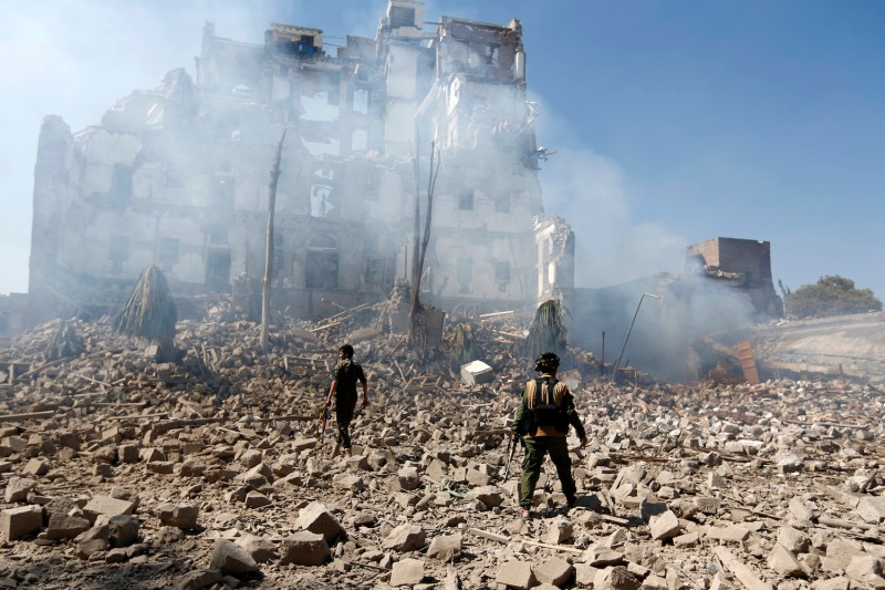 Houthi rebel fighters inspect damage.