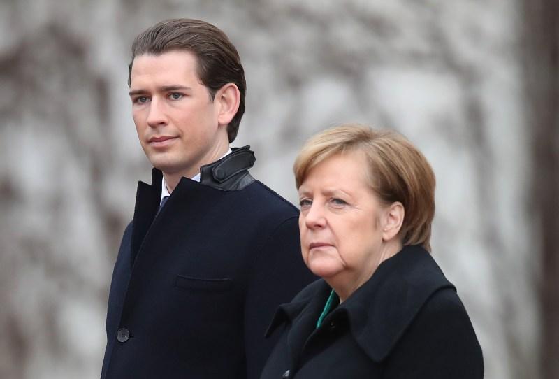 German Chancellor Angela Merkel and new Austrian Chancellor Sebastian Kurz listen to their countries' respective national anthems upon Kurz's arrival at the Chancellery on Jan. 17, 2017 in Berlin.
