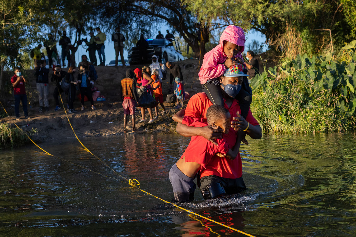 A Haitian migrant carries his children across the Rio Grande to Del Rio, Texas, from Ciudad Acuna, Mexico, on Sept. 23. John Moore/Getty Images