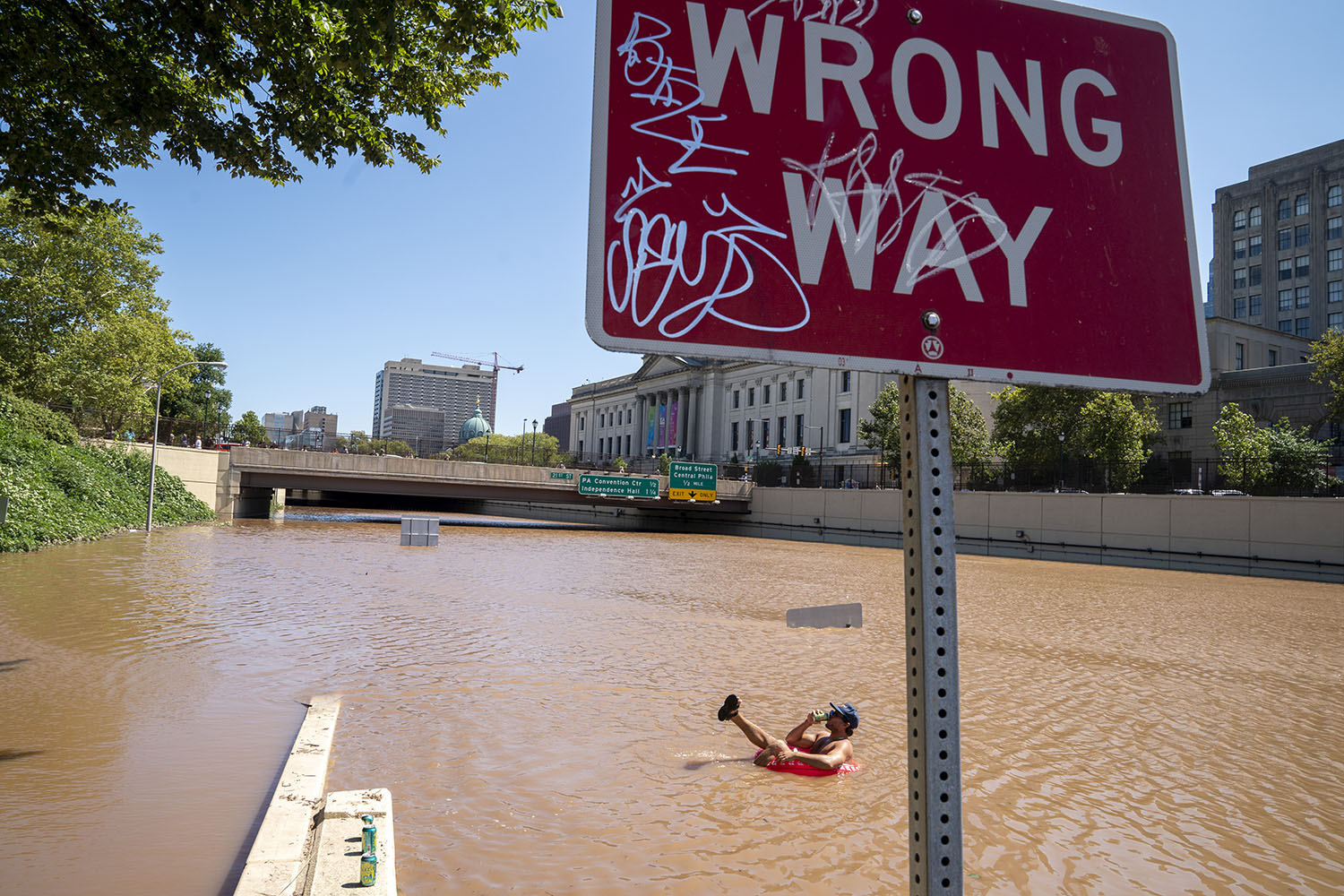 Austin Ferdock drinks a beer while floating in floodwater following a storm caused by the remnants of Hurricane Ida in Philadelphia on Sept. 2. Jessica Kourkounis/Getty Images
