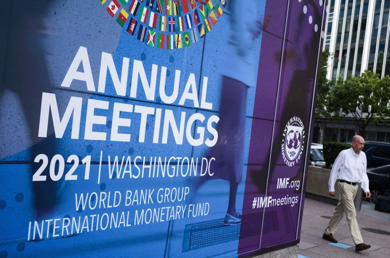 A man walks past a poster announcing the upcoming annual meeting of the World Bank and International Monetary Fund.