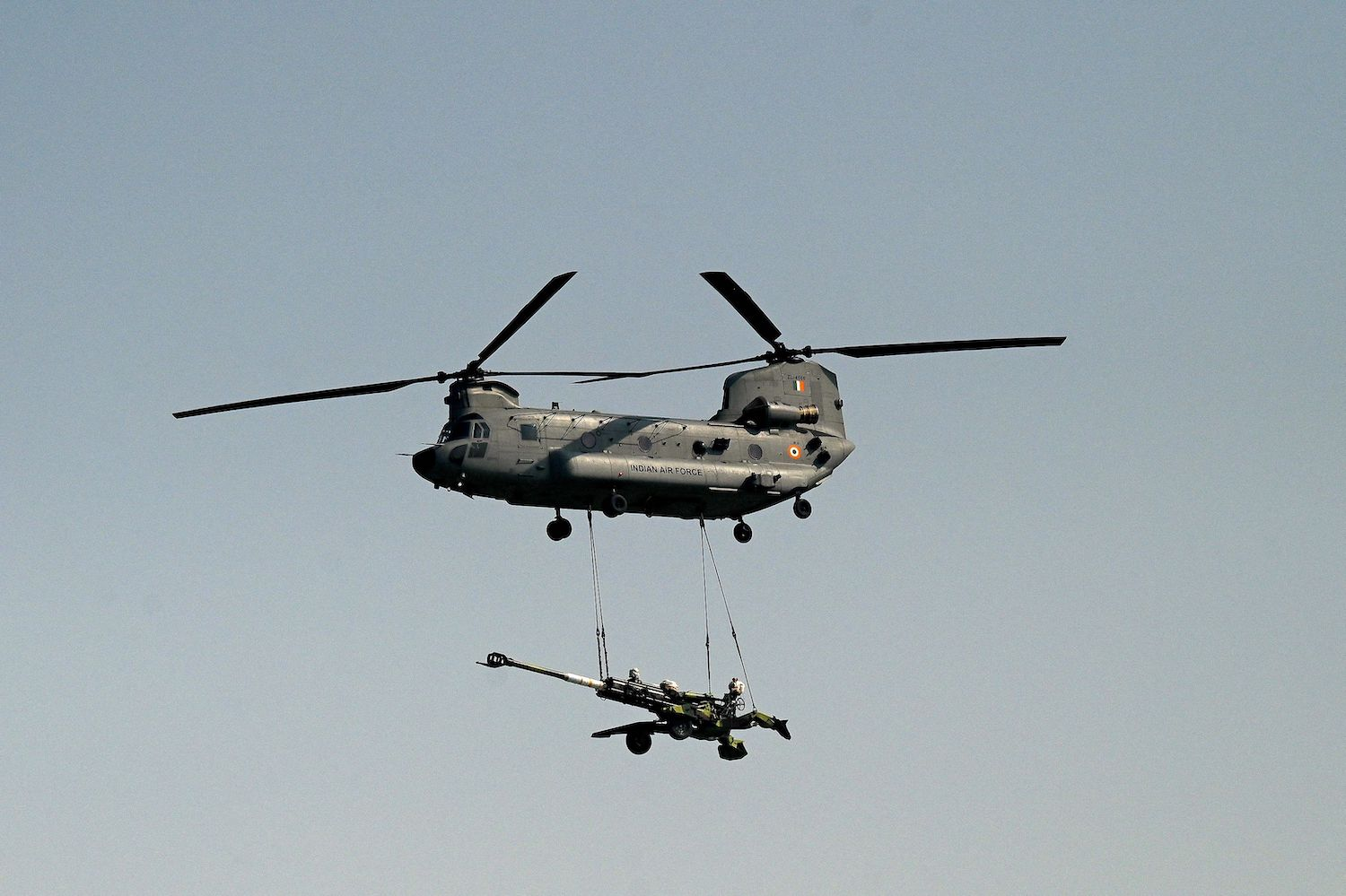 An Indian Air Force Chinook helicopter carries an artillery gun during a military parade.