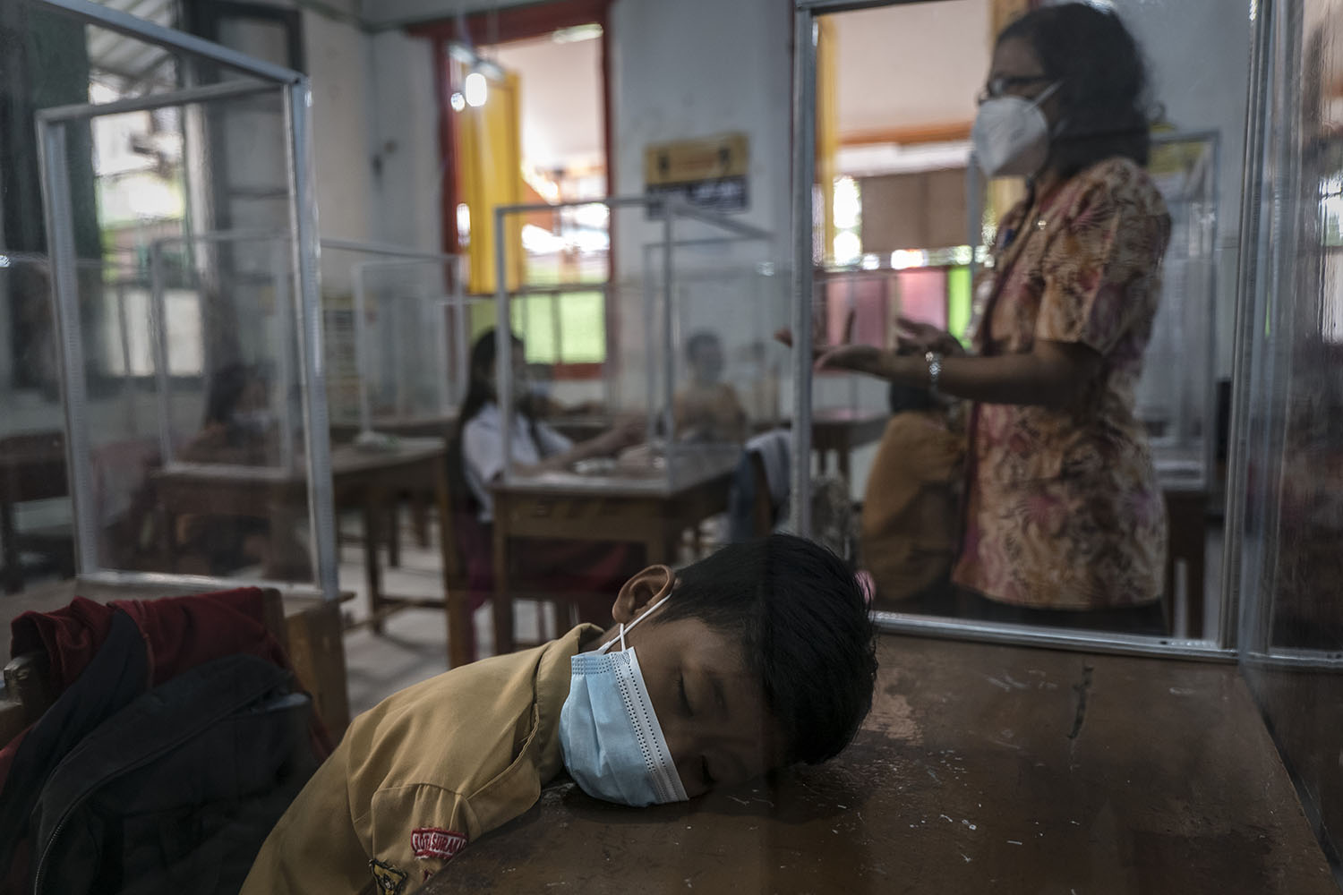 A student naps at a desk with plastic screens used for social distancing during a class at an elementary school in Solo City, Central Java, Indonesia, on Sept. 3. Ulet Ifansasti/Getty Images