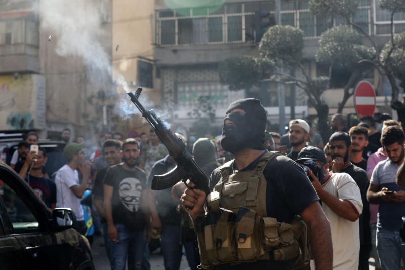 A member of Lebanon's Hezbollah movement fires his gun.