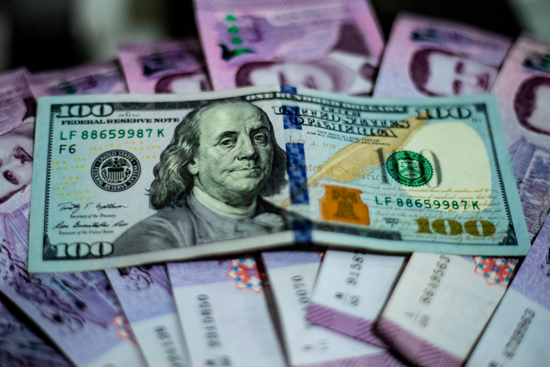 A U.S. $100 bill is placed on a stack of Syrian pounds