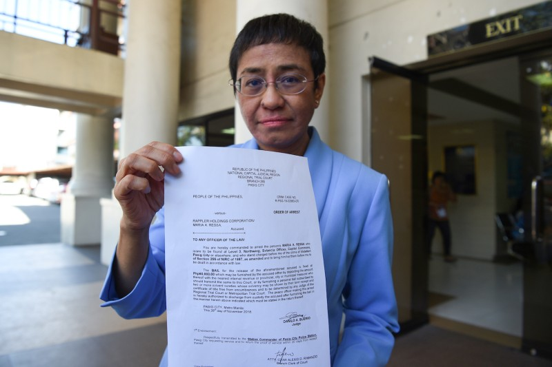 Maria Ressa holds up the warrant of arrest order after posting bail at a court in Manila.