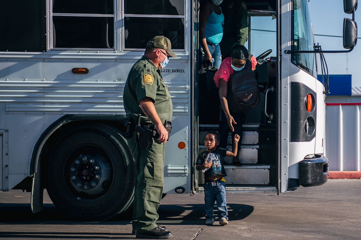 Migrants exit a Border Patrol bus and prepare to be received by the Val Verde Humanitarian Coalition in Del Rio, Texas, on Sept. 22. Brandon Bell/Getty Images