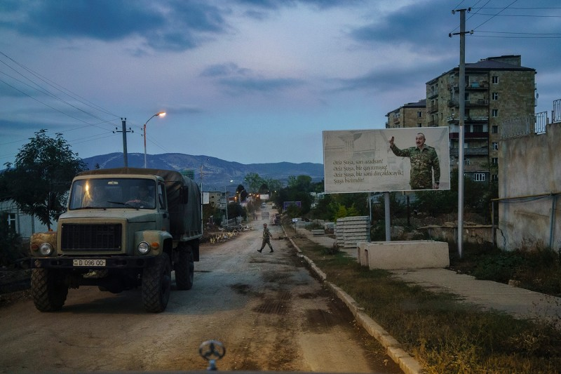 """The Azerbaijani army patrols the streets of Shusha on Sept. 25 under a sign that reads: """"Dear Shusha, you are free. Dear Shusha, we are back. Dear Shusha, we will resurrect you. Shusha is ours."""""""