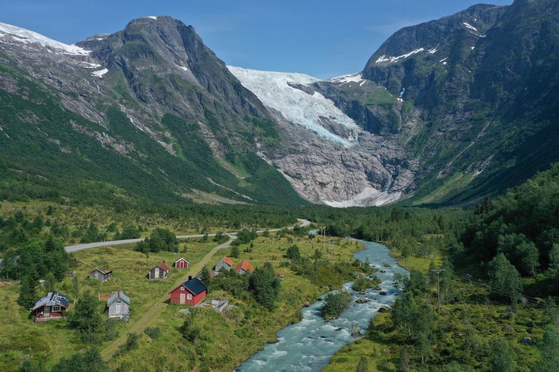 A glacier sits above a stream running past cabins in Norway.