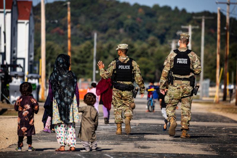 U.S. military police walk past Afghan refugees.